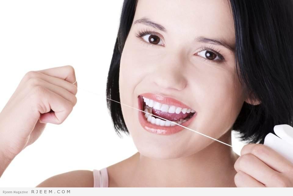 فتاة تنظف اسنانها بالخيط