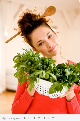 Young woman with herbs, wooden spoon in hair