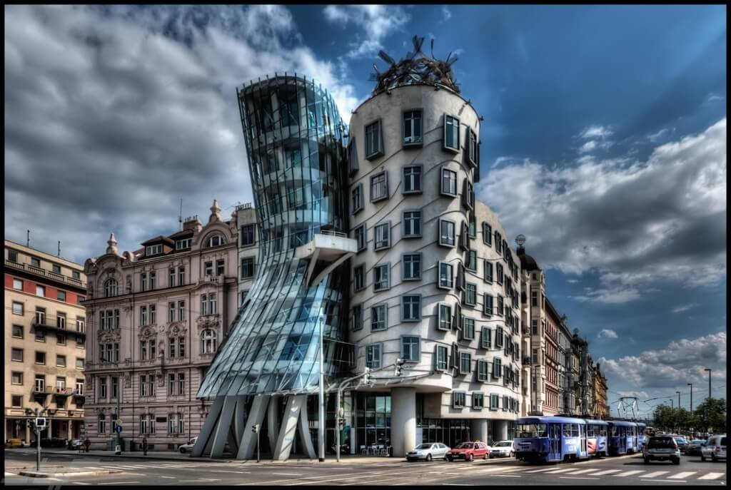I have about 500 shots of the Dancing House in Prague from every possible angle, portrait and landscape. They've been sitting on my disk for almost 2 years. I didn't know how to process them as the light was not great and an early attempt using Photomatix was a disaster. ISO 100, 14mm, f6.3, (1/1600, 1/400, 1/100 secs). I chose the f-stop so that I would get fast enough speed for the moving cars. Blended and tonmeppaed in Photomatix using Details Enhancer. Reduced noise in Imagenomics Noiseware. Carefully straightened the vertilcals using the Lens Correction filter in PS as the whole point if the building is it's vertical lines. Used the Freaky Details technique to get lots of details on the windows, etc. Used Nik Viveza to reduce the white glow around the building that was left over from Photomatix processing (masking the clouds). Used 15% Nik Glamour Glow to reduce the harshness of the Photomatix and Freaky Details.