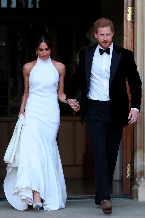 dbfb028c51851 وخلال حفل الاستقبال المسائي، استبدلت ميغان فستان الزفاف بآخر لونه أبيض  زنبقي ذي فتحة عنق تغطي رقبتها، صمَّمته مصممة الأزياء البريطانية ستيلا  مكارتني.